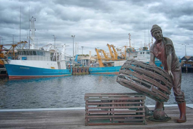 Bronze statue of a fisherman stacking baskets at Fremantle Fishing Boat Harbour
