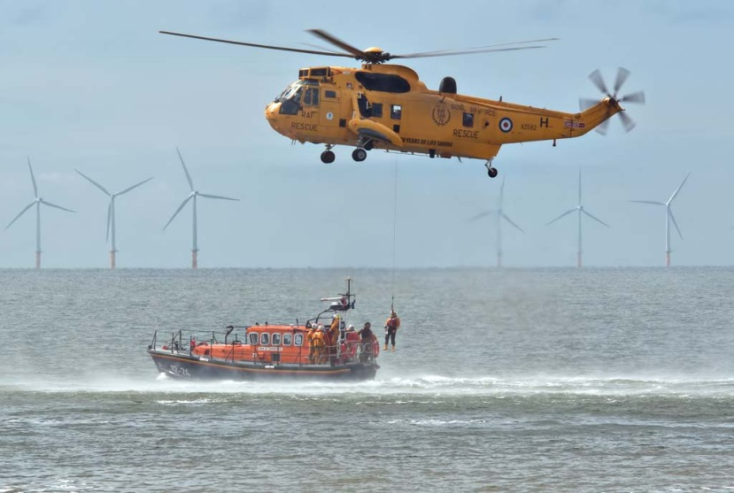 RNLI Lifeboat and Royal Air Force Rescue Helicopter practice transferring rescued person from helicopter to lifeboat