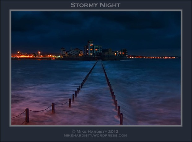 Stormy night at Knightstone Island with the waves breaking over the causeway